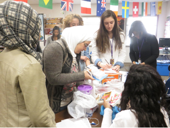 Facing History Girls Group members sort household goods donations for immigrants' apartments.