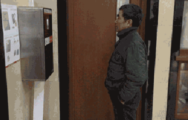 Man standing at a toilet paper dispenser